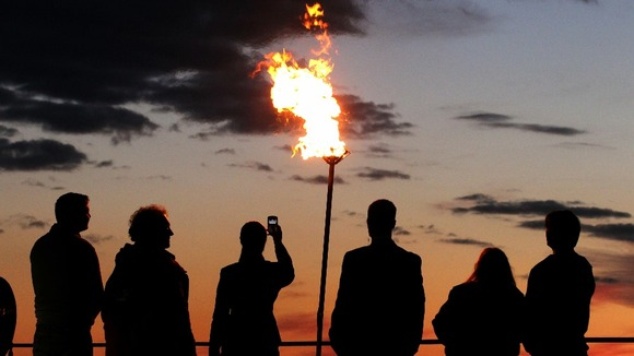 People view the Diamond Jubilee beacon at Edinburgh Castle beside Mons Meg Cannon as the sunsets
