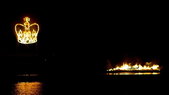 A crown shaped firework is lit behind the Holme Pierrepont Beacon which is floating on the Regatta in Nottingham