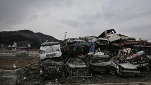 Cars destroyed by the March 11 tsunami are left abandoned as the 330 ton fishing vessel which was flung 800 metres
