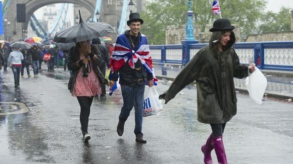 Rain soaks revellers celebrating the queen's Diamond Jubilee, after they watched the river pageant at Tower Bridge in London.