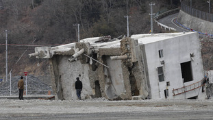 Visitors look at a fallen building in the neighborhood destroyed by the tsunami