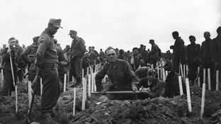 German soldiers captured by American forces bury some of the men killed during the assaults.