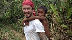 Beckham in the Amazon Rainforest with a child from a local tribe.