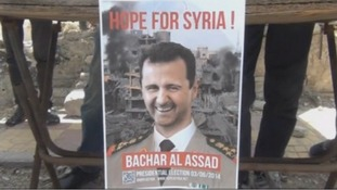 An election poster with the smiling face of Assad in front of a destroyed building in Ghouta, Syria