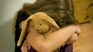 File photo of a girl crying in with cuddly toy.