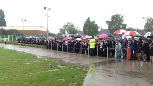 Pupils and staff wait in the rain for Prince William's arrival