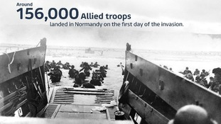 Troops wade ashore from a landing craft in Normandy.
