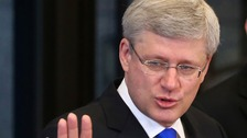 Prime Minister Stephen Harper has paid tribute to the police officers killed in Brunswick, Canada, as a manhunt for the gunman continues.