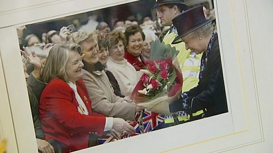 A picture of Margaret handing the Queen a bunch of flowers.