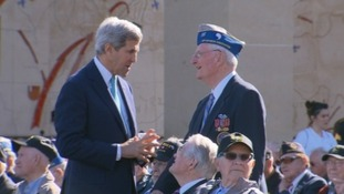 US Secretary of State John Kerry chats to one of the veterans ahead of a memorial service at the US cemetery.