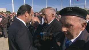 President Francois Hollande greets French veterans at a memorial event at Caen.