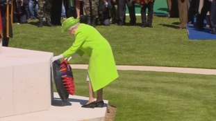 The Queen lays a wreath as the ceremony takes place.