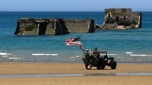 A vintage US Army jeep is driven past the remains of a Mulberry harbour on Gold Beach.