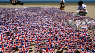 Volunteers plant some of 22,000 Union Jack flags with handwritten notes of gratitude to allied soldiers on Asnelles beach.