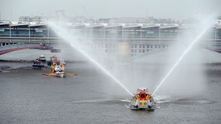 The Gloriana with the Queen's Baton on board receives a water spraying guard of honour from the London Fire Brigade