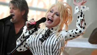 Dolly Parton with mic performing on NBC