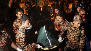 Malaysian police remove Mr Huntley's body following its discovery more than a week after he went missing