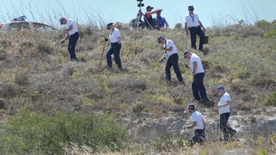 British police officers pictured searching an area of scrubland last week in the hunt for Madeleine McCann.