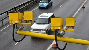 Cars drive underneath motorway speed cameras