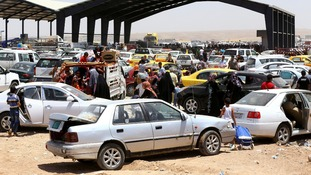 Families fleeing the violence in the Iraqi city of Mosul arrive at a checkpoint at Iraq's Kurdistan region.
