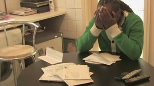 An actor is faced with a pile of bills in the video for We Need A Union On The Streets.