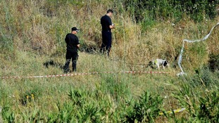 Police use sniffer dogs to search a patch of scrubland just outside Praia da Luz.