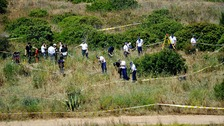 British police and their Portuguese counterparts search a patch of scrubland in the Madeleine McCann investigation.