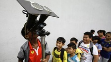 Children take turns to look at planet Venus transiting across the sun at a public viewing at the Singapore Science Centre