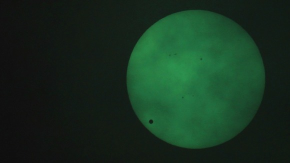 The planet Venus transits across the sun, as seen through a welding filter in Sydney