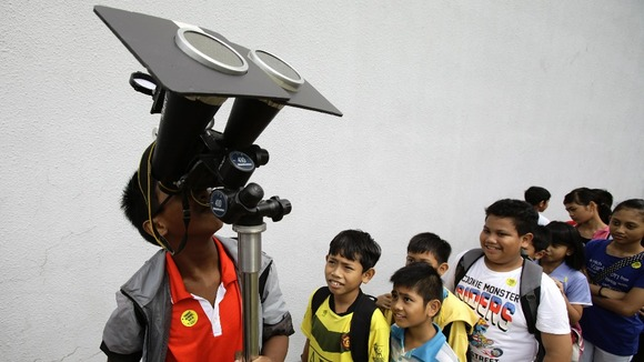 Children take turns to look at planet Venus transiting across the sun at a public viewing at the Singapore Science Centre. 