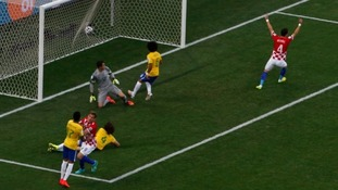 Marcelo, centre, watches as his scuffed clearance hits the back of the net.