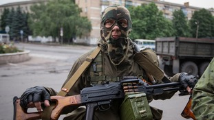 An armed pro-Russian separatist looks on at a town center in Snizhnye in eastern Ukraine, yesterday.