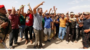 New recruits to the Iraqi army sing and chant before boarding buses to Iraq.