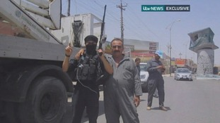 An ISIS fighter poses for the camera with an electricity worker.