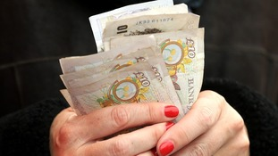Woman holds money £10 notes in hands.