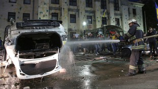 Firefighters pour water onto a damaged car as protesters hold a rally near the Russian embassy in Kiev.