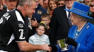 Queen Elizabeth II presents Lydon Lea of the Zacara team with the Queen's Cup trophy.