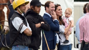 Prince George appears more interested in the grass than watching his father and uncle play polo.