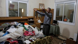 A man gestures after his home is searched and belongs strewn by Israeli soldiers.