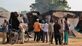 Residents stand in front of torched buildings in Mpeketoni, Kenya.
