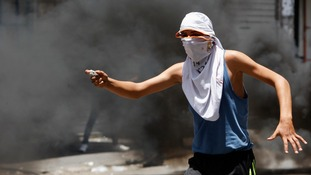A Palestinian is seen throwing a stone at Israeli soldiers in Hebron.