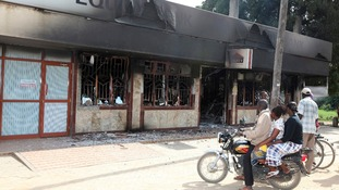 Townspeople look at a burnt-out shop in Mpeketoni, the morning after the raid.