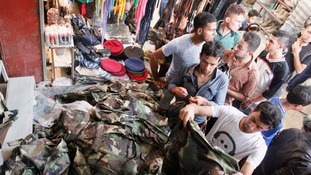 Men buy military kit from a stall in Basra, Iraq.