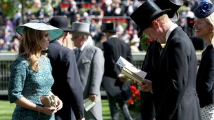 Prince Harry studies his race card, next to his cousin Princess Beatrice.