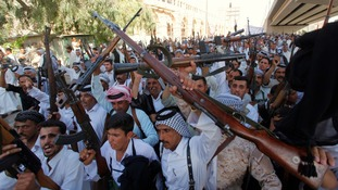 Tribal fighters shout slogans while holding weapons during a parade on a street in Najaf, south of Baghdad.