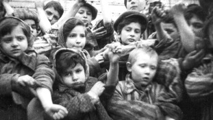 Children who survived Auschwitz II-Birkenau display their tattooed identification numbers.