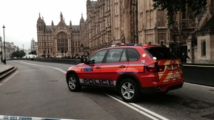 A police car is shown within the cordoned-off area in Westminster.
