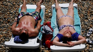 Sunbathers relax on Brighton beach.