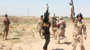 Members of the Iraqi security forces shout slogans as they carry weapons during clashes with Sunni militant group Isis.