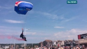 Spectators can be heard gasping as the parachutist begins to land early, failing to hit his drop zone.